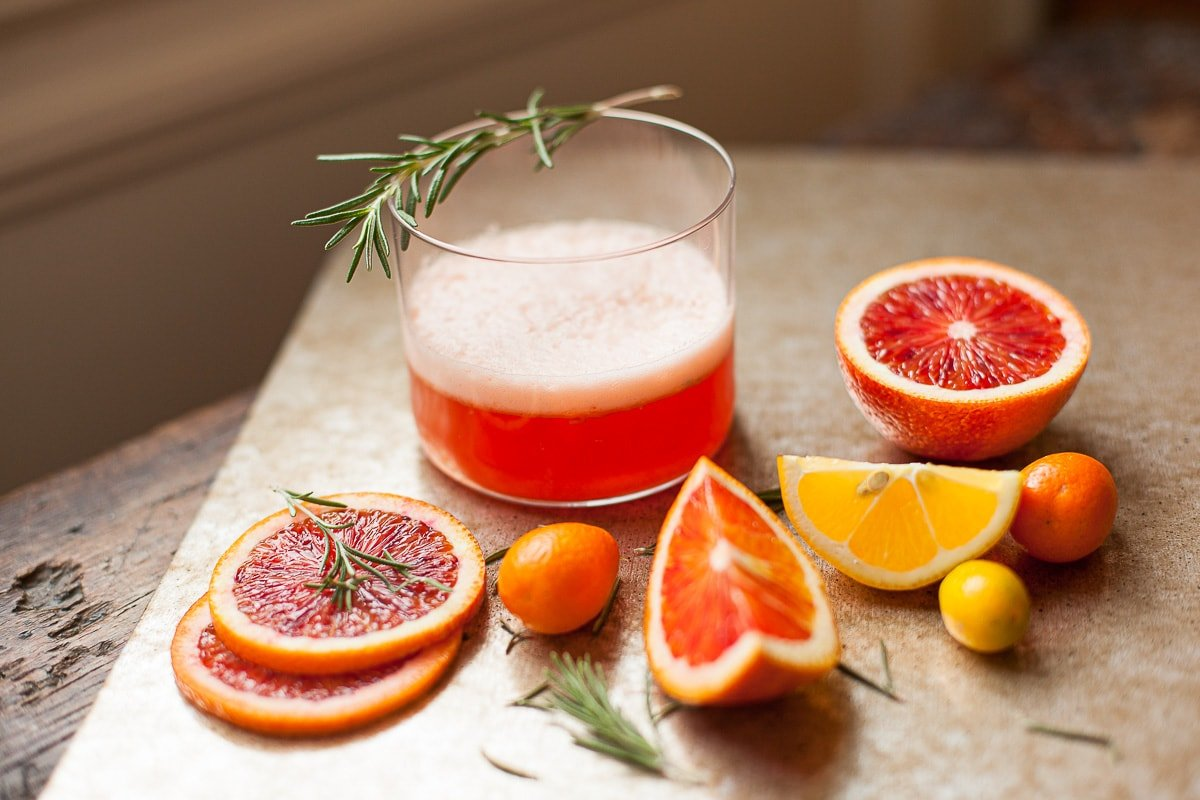 A glass of blood orange negroni cocktail with slices of blood orange, meyer lemon and kumquats.