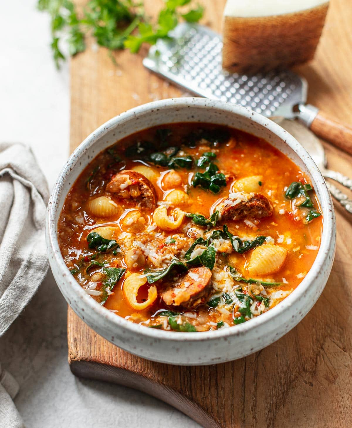 A gray bowl on a wooden cutting board filled with chunky garbanzo bean soup with chorizo, kale and shredded cheese.