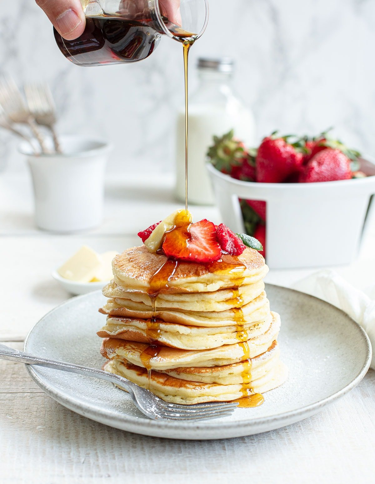 Maple syrup pouring over a stack of thick and fluffy buttermilk pancakes on a gray plate, topped with sliced strawberries, a pat of butter.