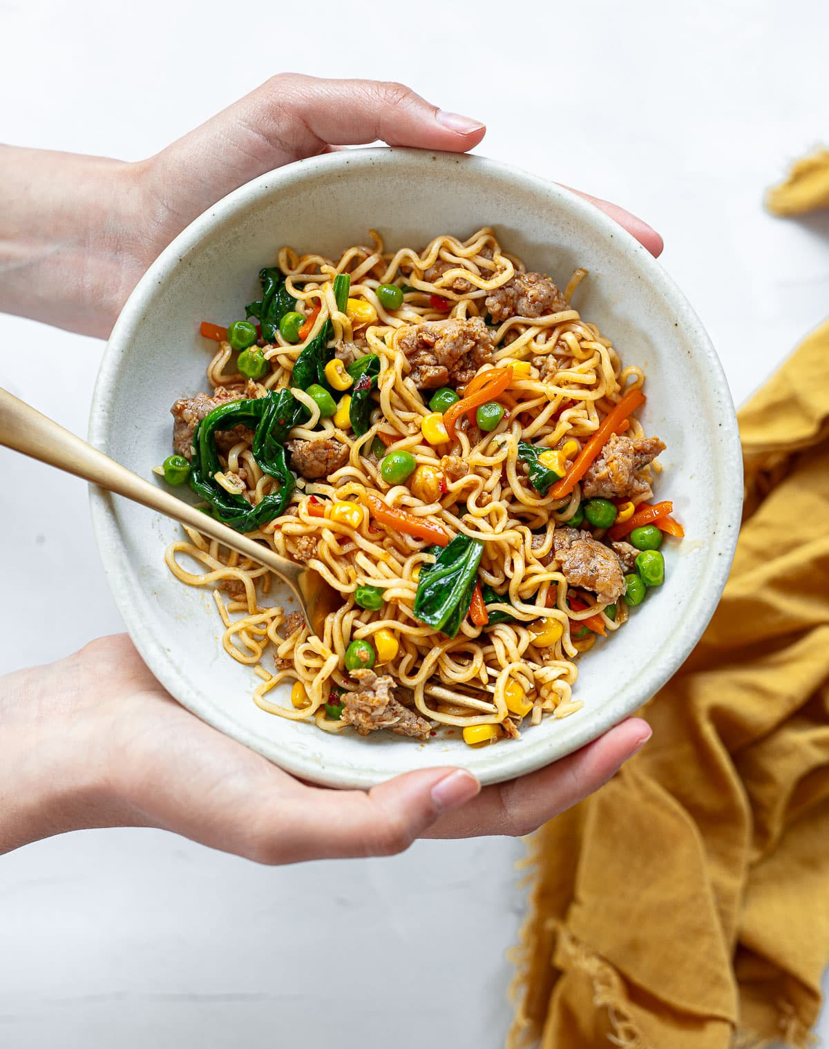 A white bowl with a gold serving fork filled with ramen noodle stir-fry mixed with peas, carrots, corn and spinach.