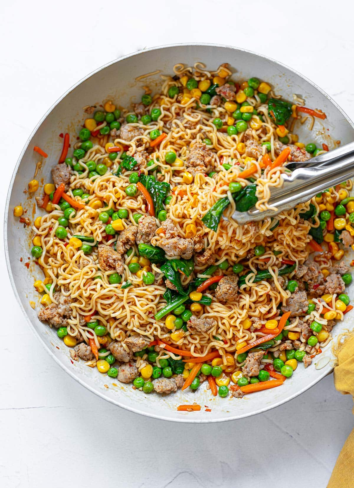 A white nonstick pan with gold serving spoons filled with ramen noodle stir-fry mixed with peas, carrots, corn and spinach.