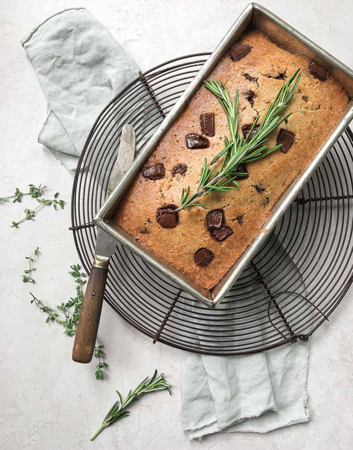 A loaf pan of olive oil quick bread topped with chocolate chunks and fresh rosemary sprig.
