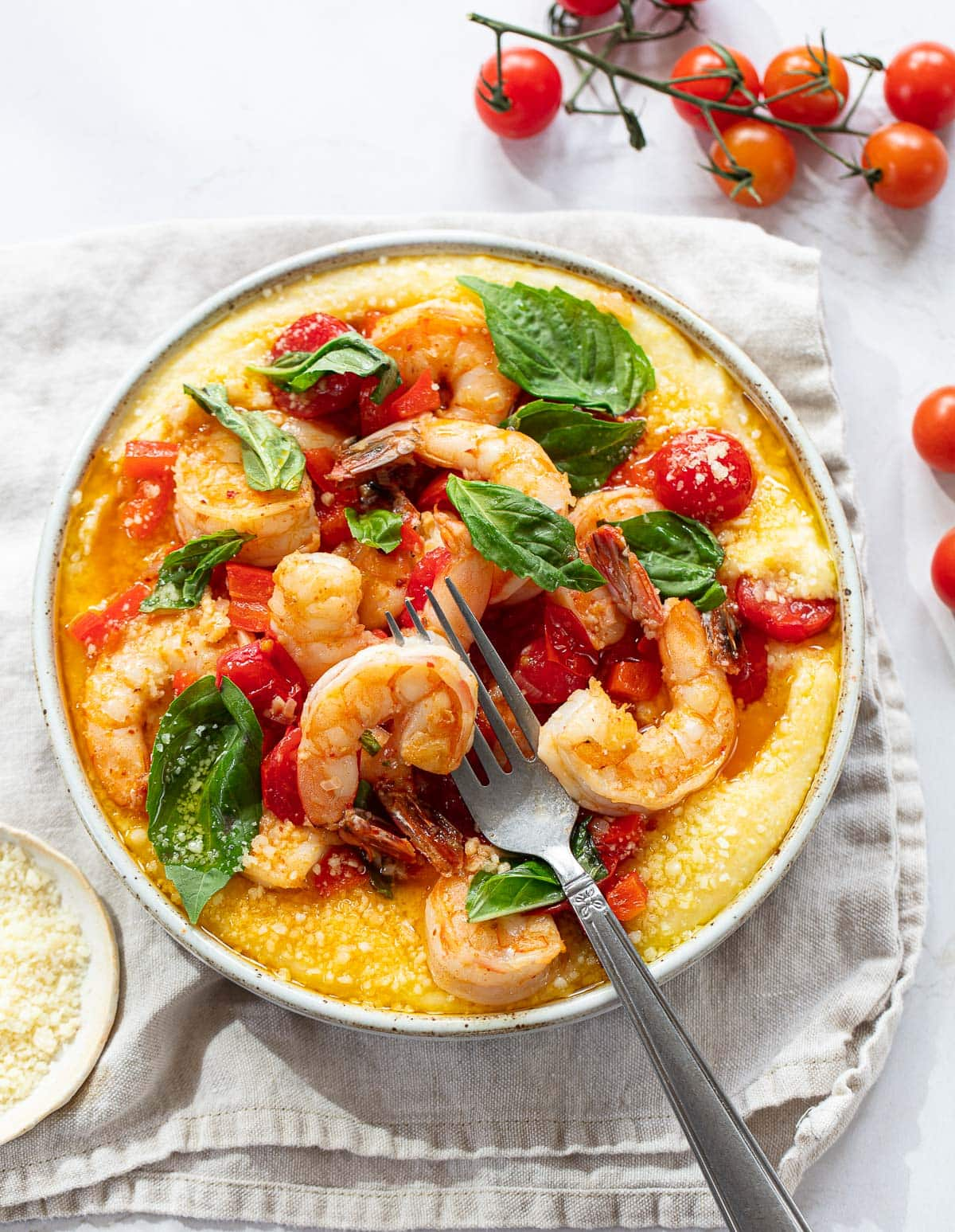 A bowl of soft creamy yellow polenta topped with whole shrimp, cherry tomatoes and fresh basil leaves.