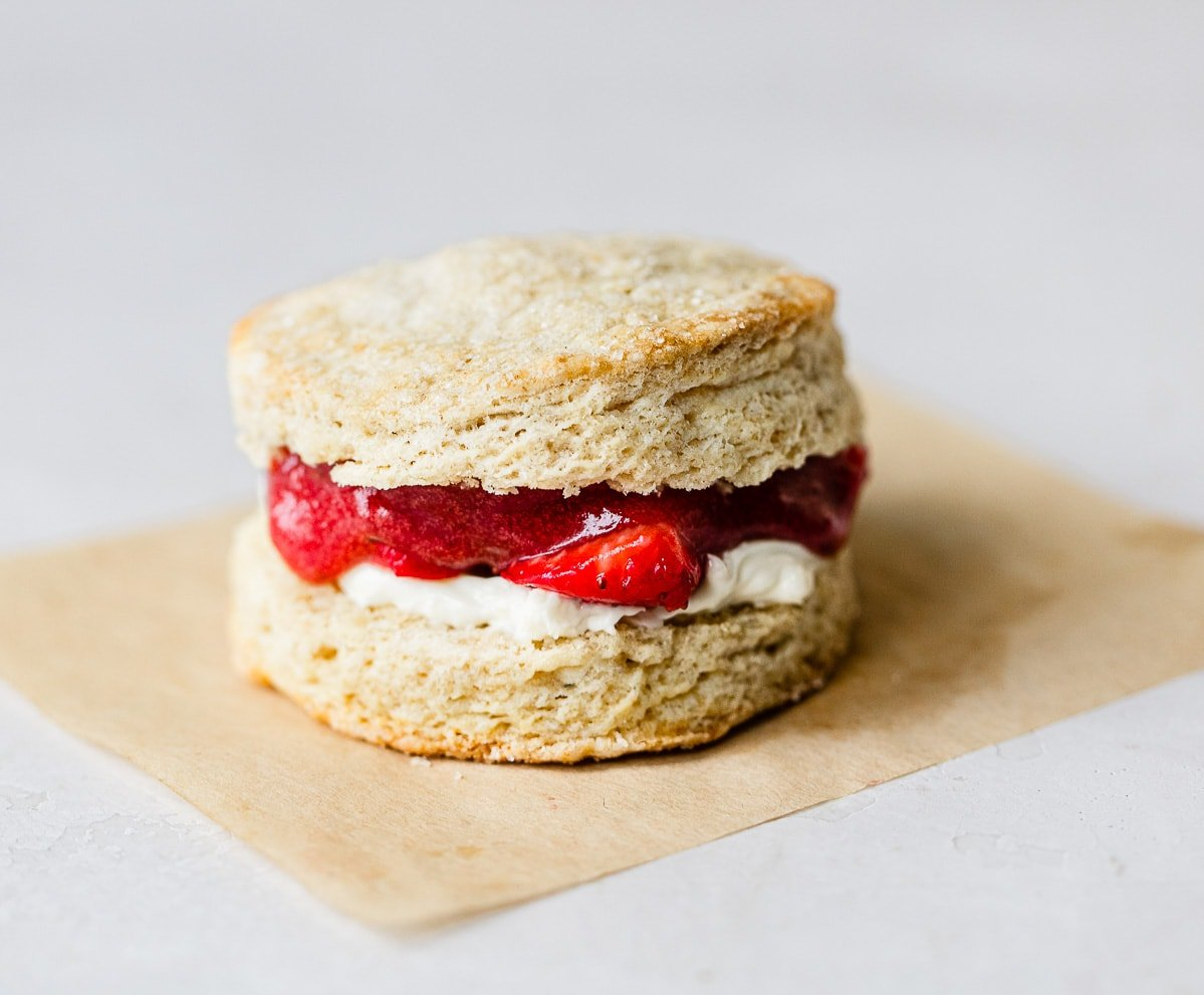 Split buttermilk biscuits with flaky layers on a piece of parchment paper and spread with mascarpone cheese, strawberry jam and fresh strawberries.
