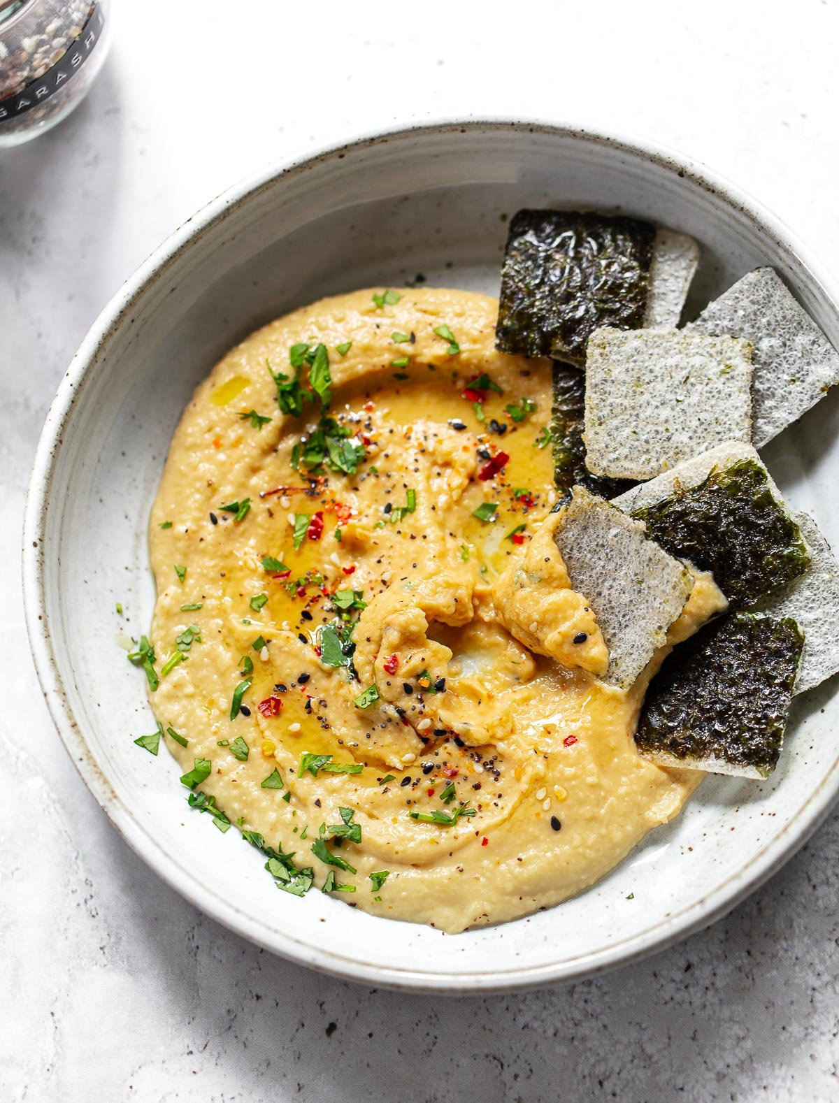 A golden yellow hummus made with miso, chickpeas and toasted sesame oil in a gray bowl. Seaweed rice crackers on the side