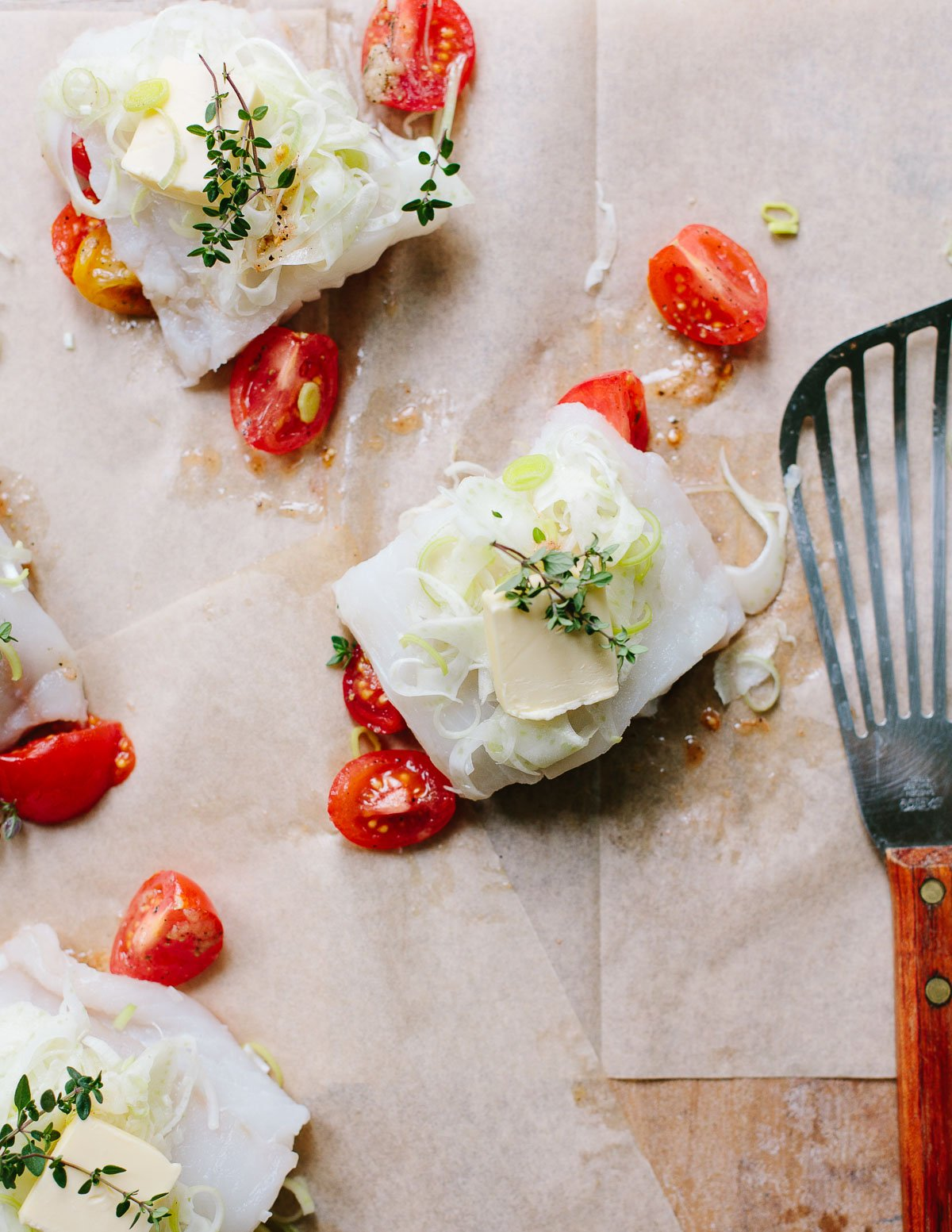 White cod fish fillets on brown parchment paper with sliced fennel bulb, cherry tomatoes, olive oil and thyme herb sprigs.