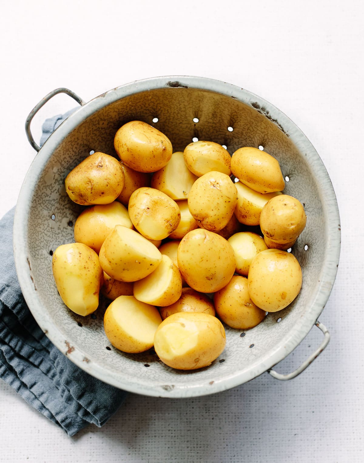A gray metal colander with small yellow Yukon Gold potatoes ready for boiling.