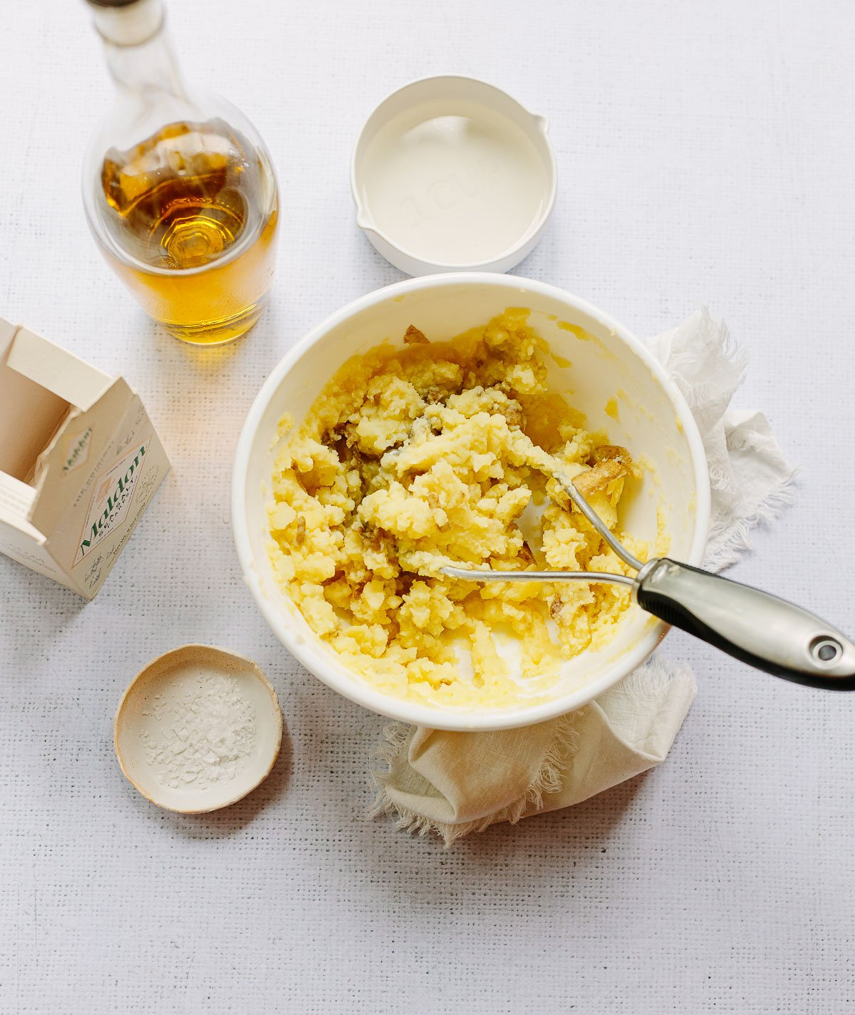 White mixing bowl with handheld potato masher blending cooked potatoes with olive oil, salt and water.