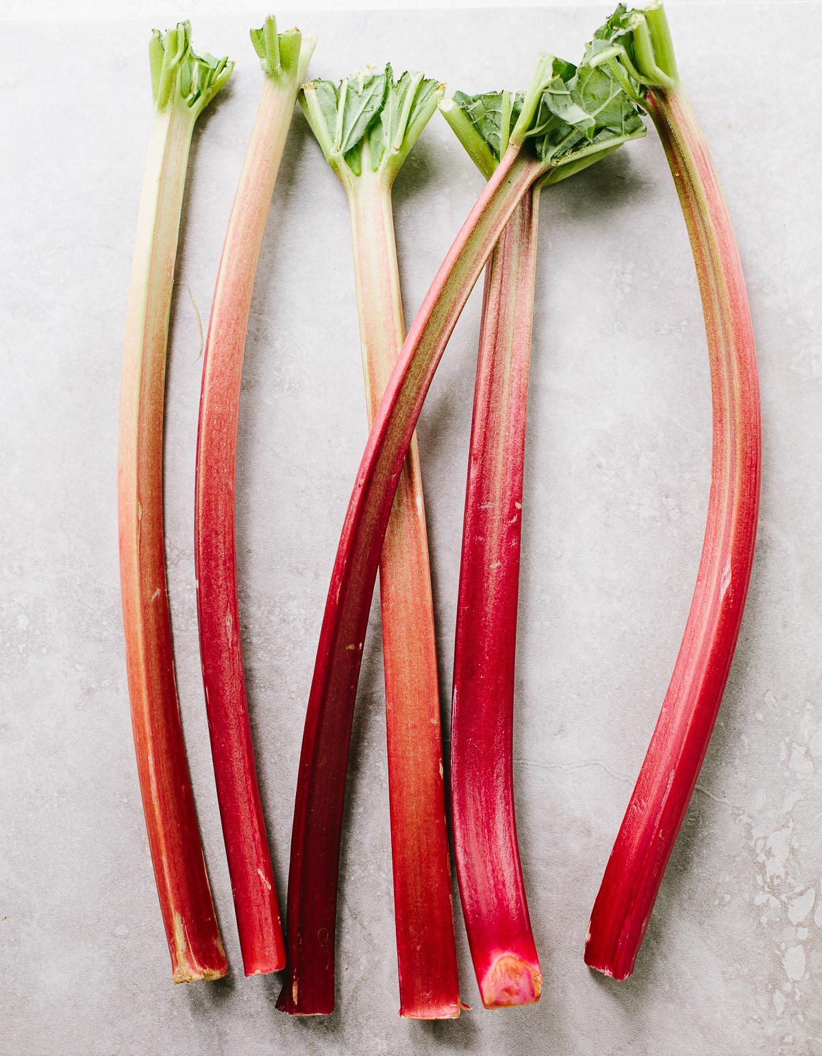 Fresh red rhubarb stalks with green tops on a gray surface.