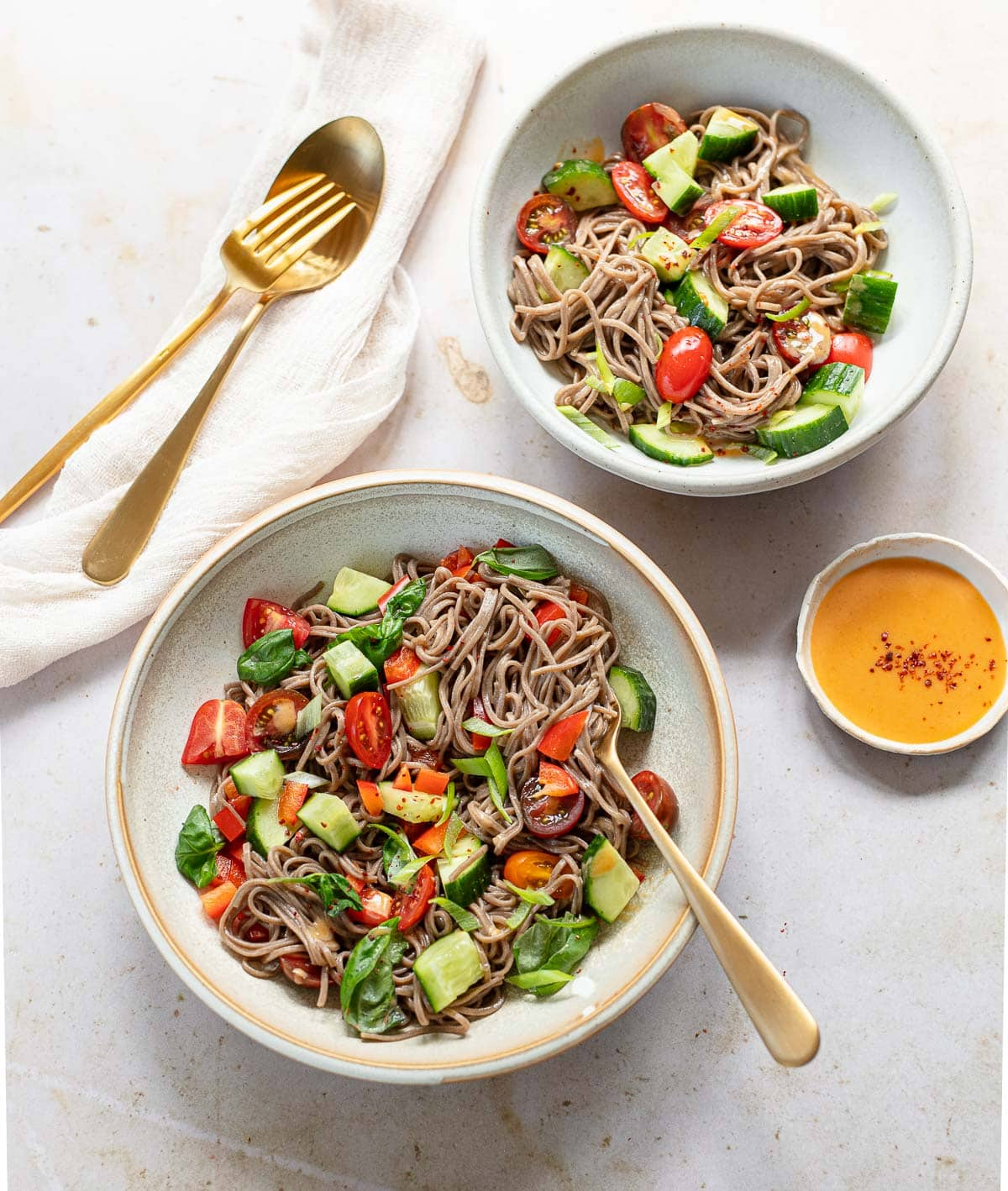 Cold buckwheat soba noodle salad tossed with cucumber, vegetables and spicy miso dressing in a bowl with a fork and dressing on the side.