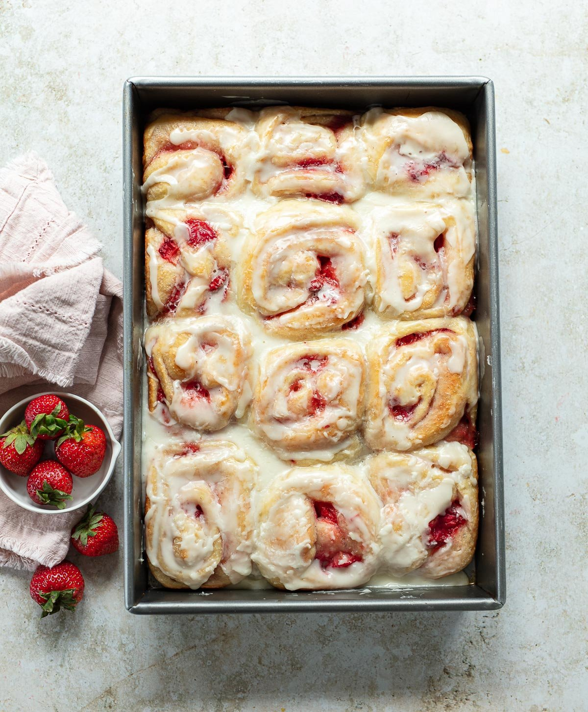 A rectangular metal baking pan filled with baked sweet rolls with swirls of strawberry filling and a creamy lemon glaze.