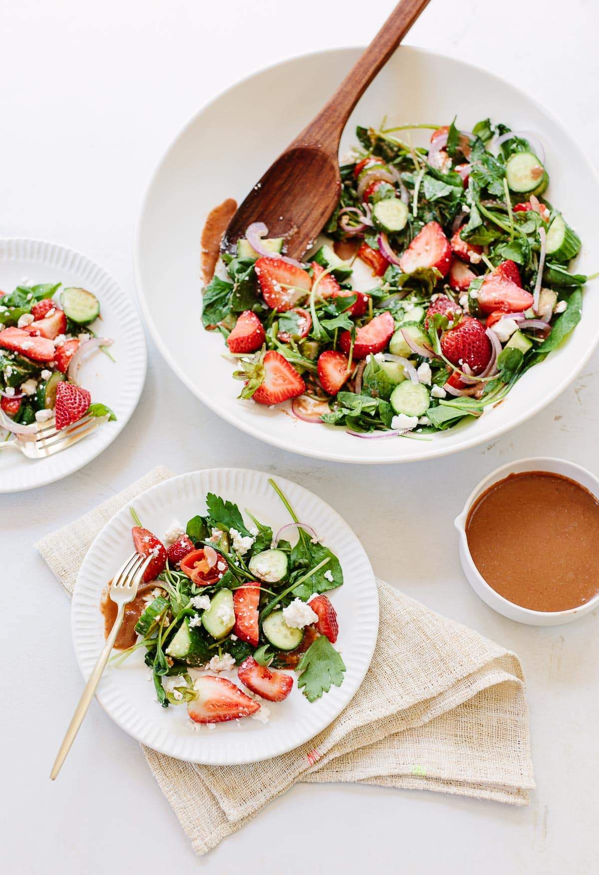 A white serving bowl with fresh strawberry salad, arugula, cucumbers, tomatoes and feta cheese.
