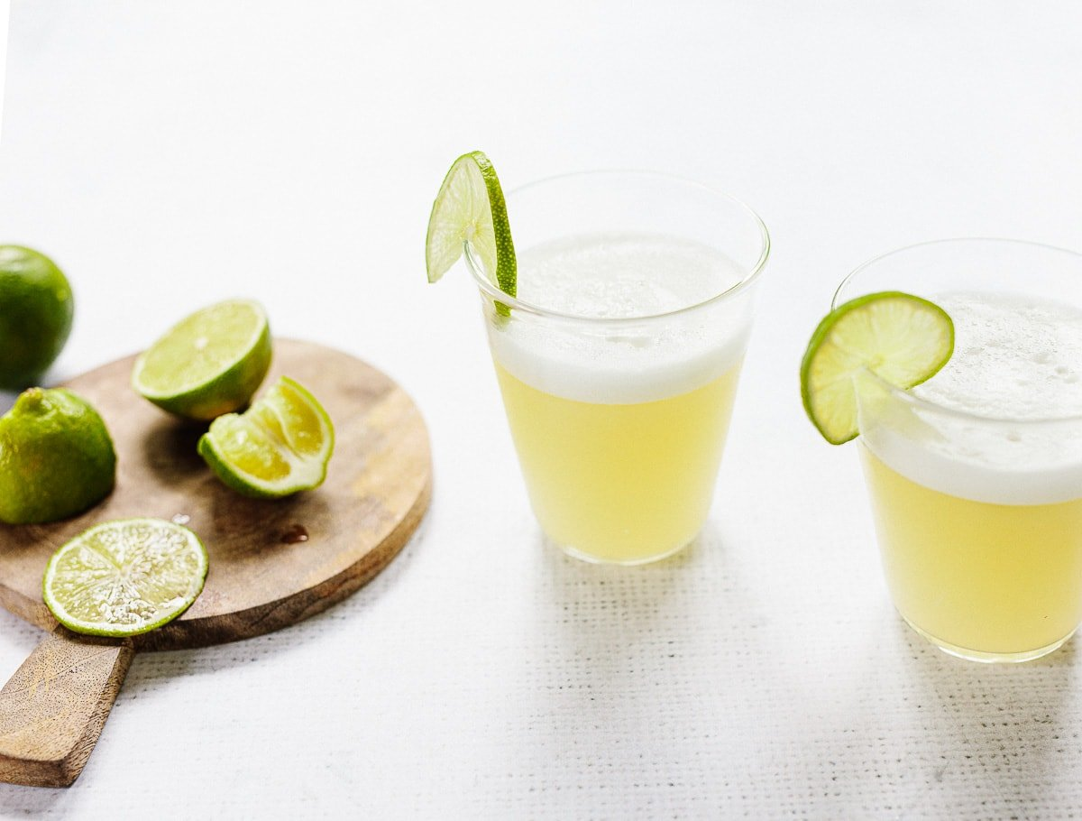 Tequila and lime cocktail in a clear rocks glass, with a foamy shaken egg white topping and fresh wedges of lime.