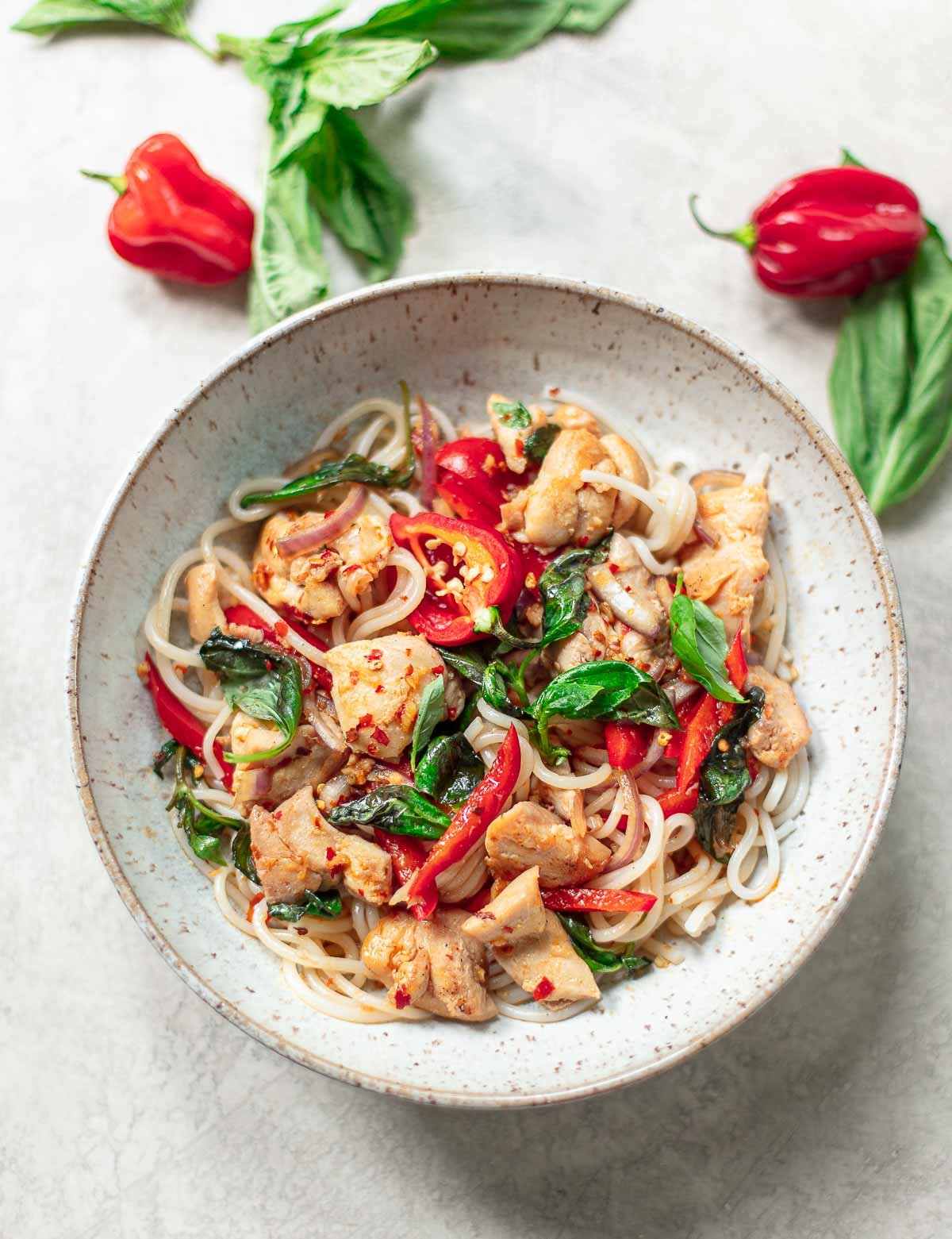 chunks of chicken in Thai basil sauce with red bell pepper, chili peppers, fresh basil and rice noodles in a gray serving bowl.