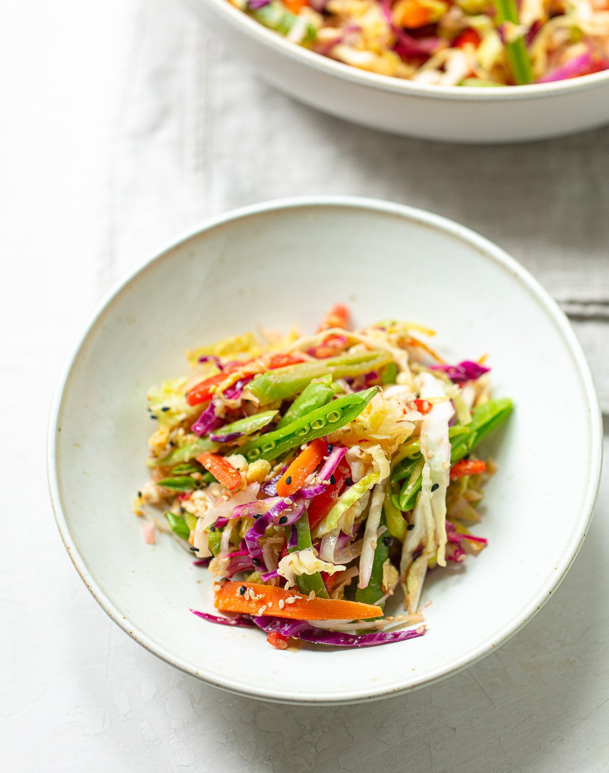 Green and red cabbage slaw mixed with carrots, snowpeas and sesame dressing in a white bowl.
