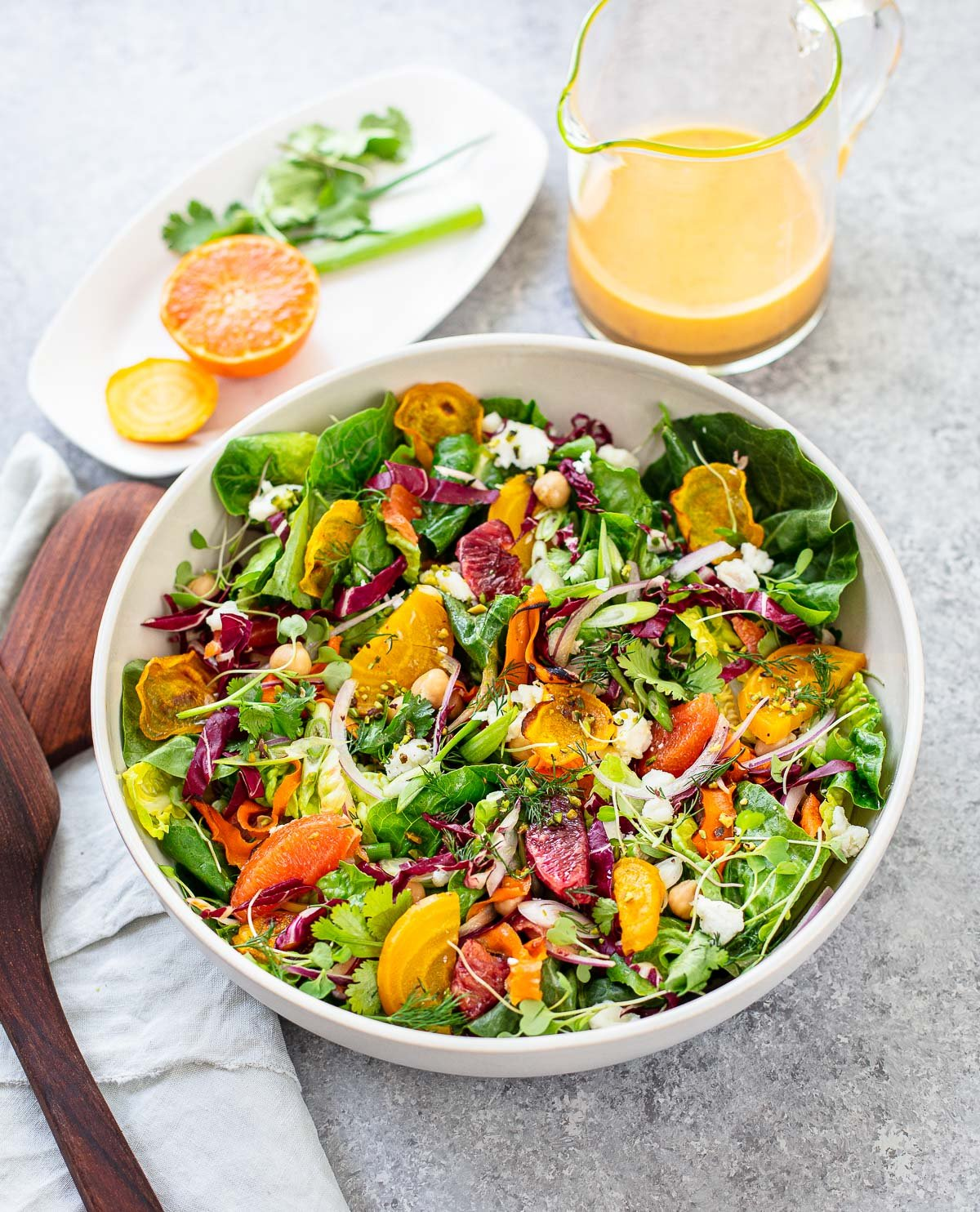 A large white salad bowl filled with orange and red roasted beets, blood orange, tangerine and orange segments and salad greens.