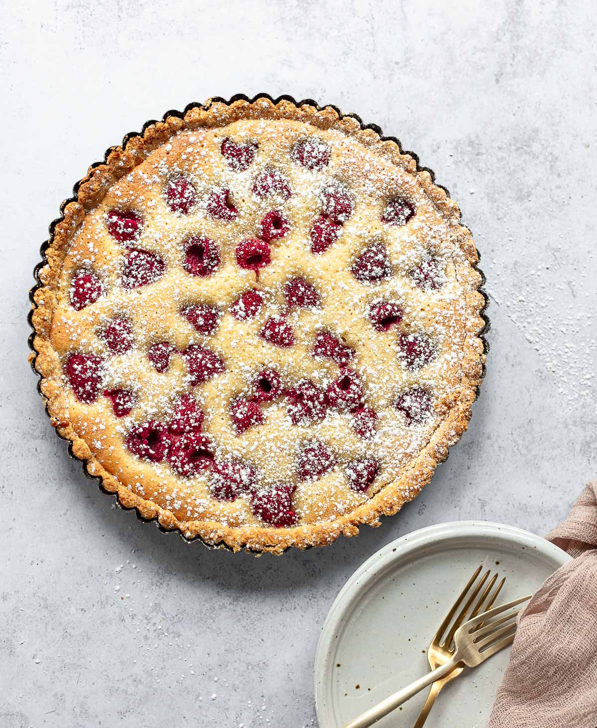 A photo of raspberry almond tart filled with baked frangipane cream and fresh raspberries, with serving plate and two forks.