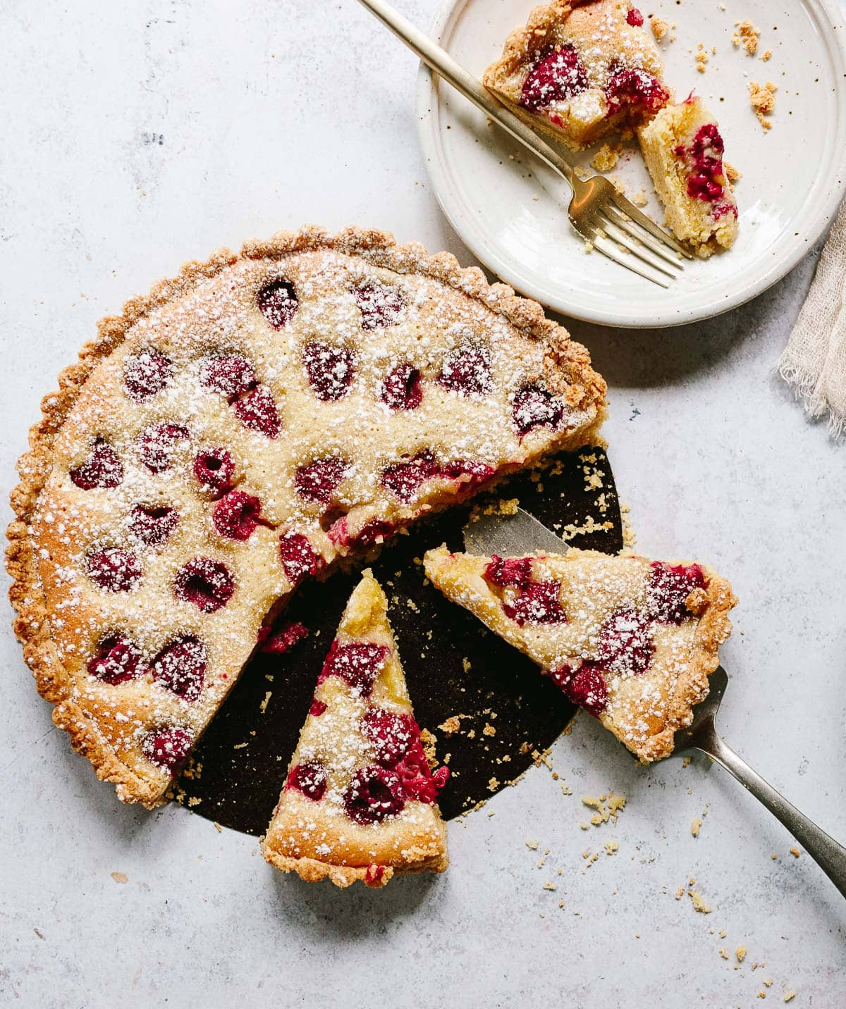 A photo of sliced raspberry almond tart filled with baked frangipane cream and fresh raspberries, with serving plate and two forks.