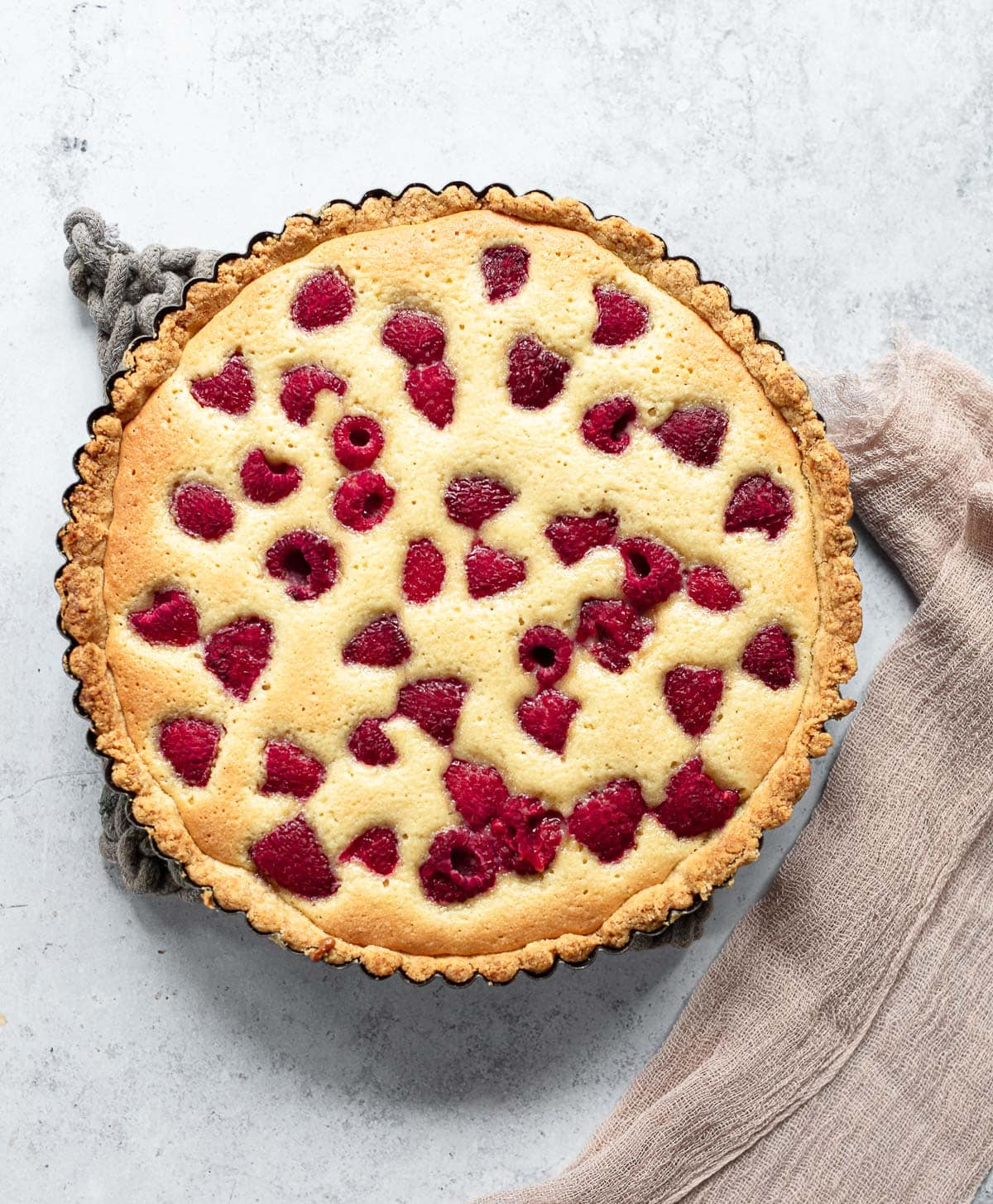 A photo of raspberry almond tart filled with baked frangipane cream and fresh raspberries