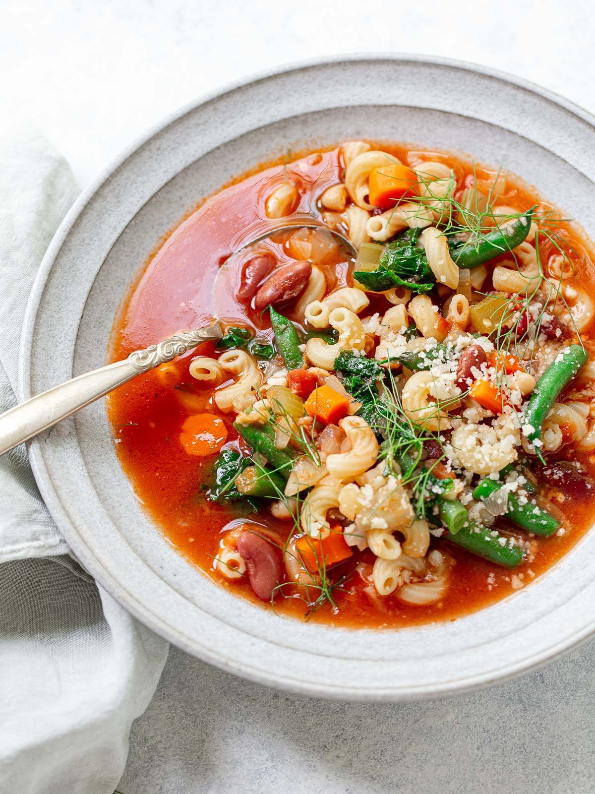 A soup bowl and spoon, with tomato-based vegetable minestrone soup with green beans, elbow macaroni, beans, carrots and grated parmesan cheese.