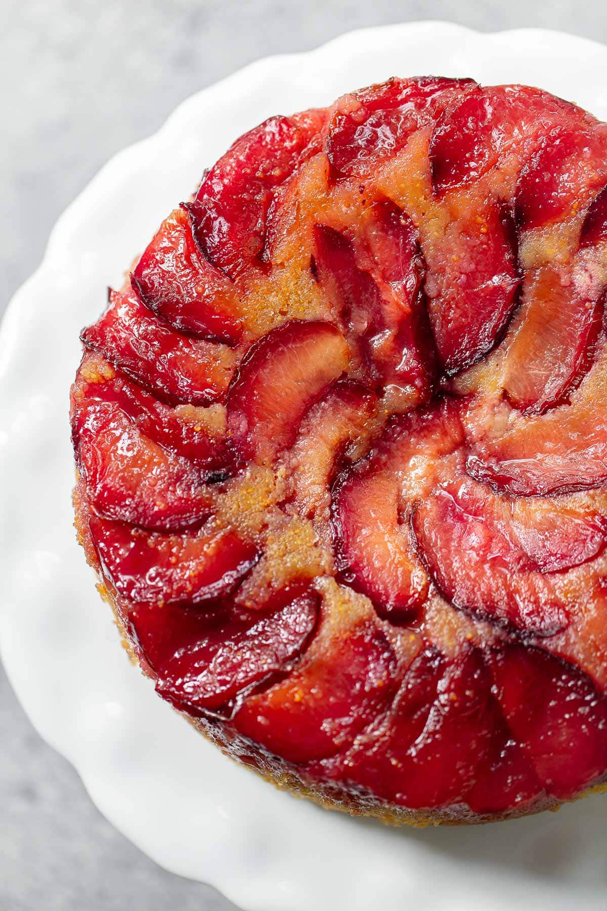 Sliced wedges of upside down plum cake with sticky sauce on a white cake stand.