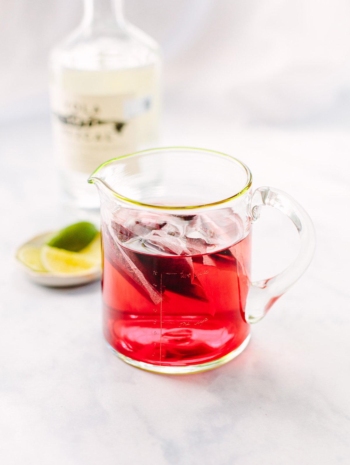 Red Hibiscus tea bags steeping in a clear measuring cup with lime slices in the background.