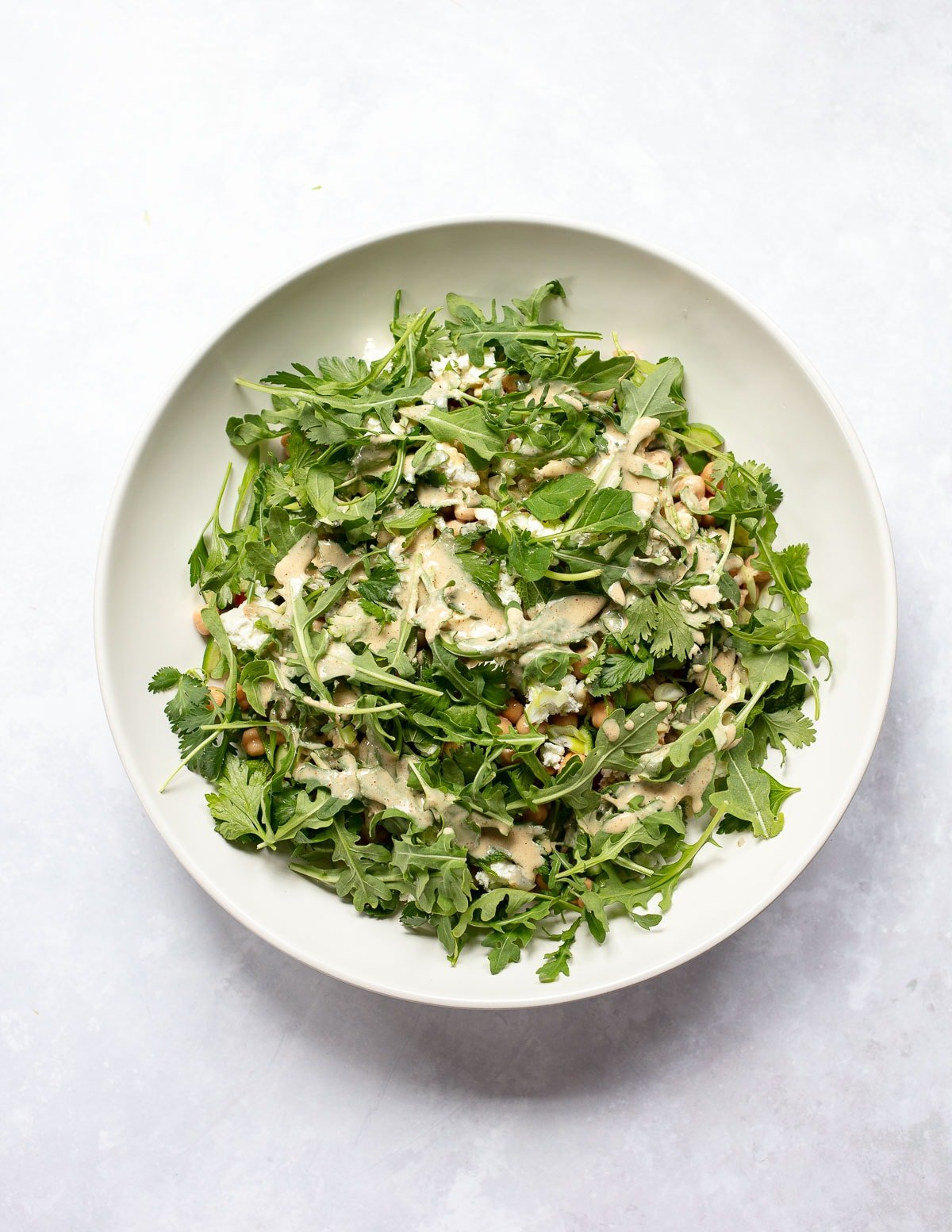 Mixed salad with baby greesn, bulgur wheat, vegetables and tahini dressing in a large serving bowl.