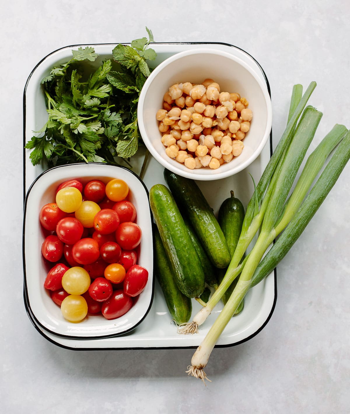 Mediterranean vegetables arranged in a tray for tabbouleh salad, with cherry tomatoes, cucumbers, chickpeas, green onions, cilantro, parsley and mint.