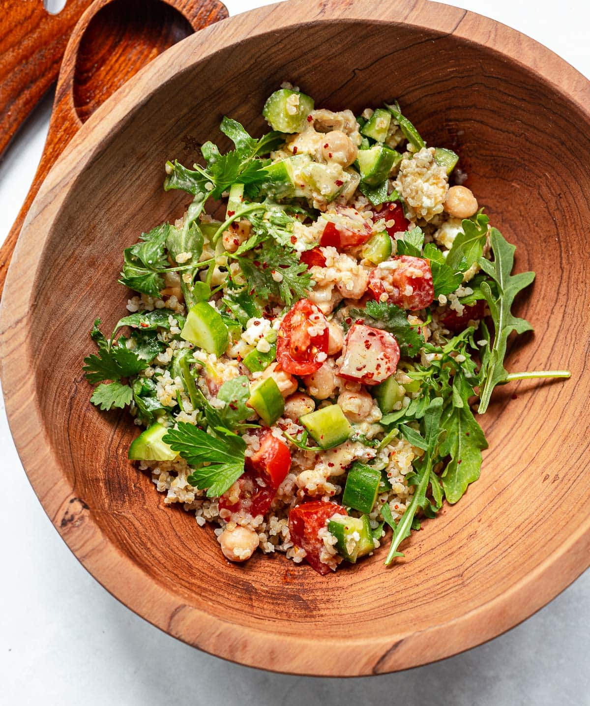 Mixed salad with bulgur wheat, vegetables and tahini dressing in a large serving bowl with wood serving utensils