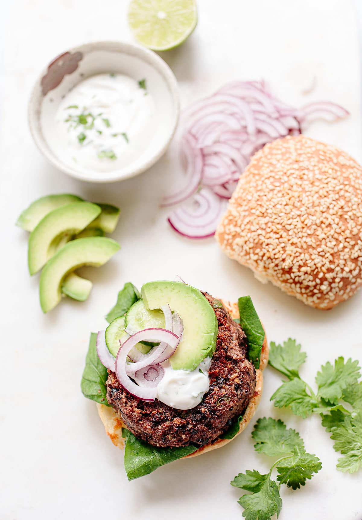 Black bean burger on a bun with avocado, greens, onion and lime mayo topping.