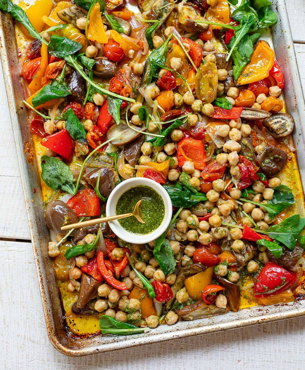 Sheet pan with roasted bell peppers, red and orange cherry tomatoes, eggplant and arugula greens with pesto sauce on the side.