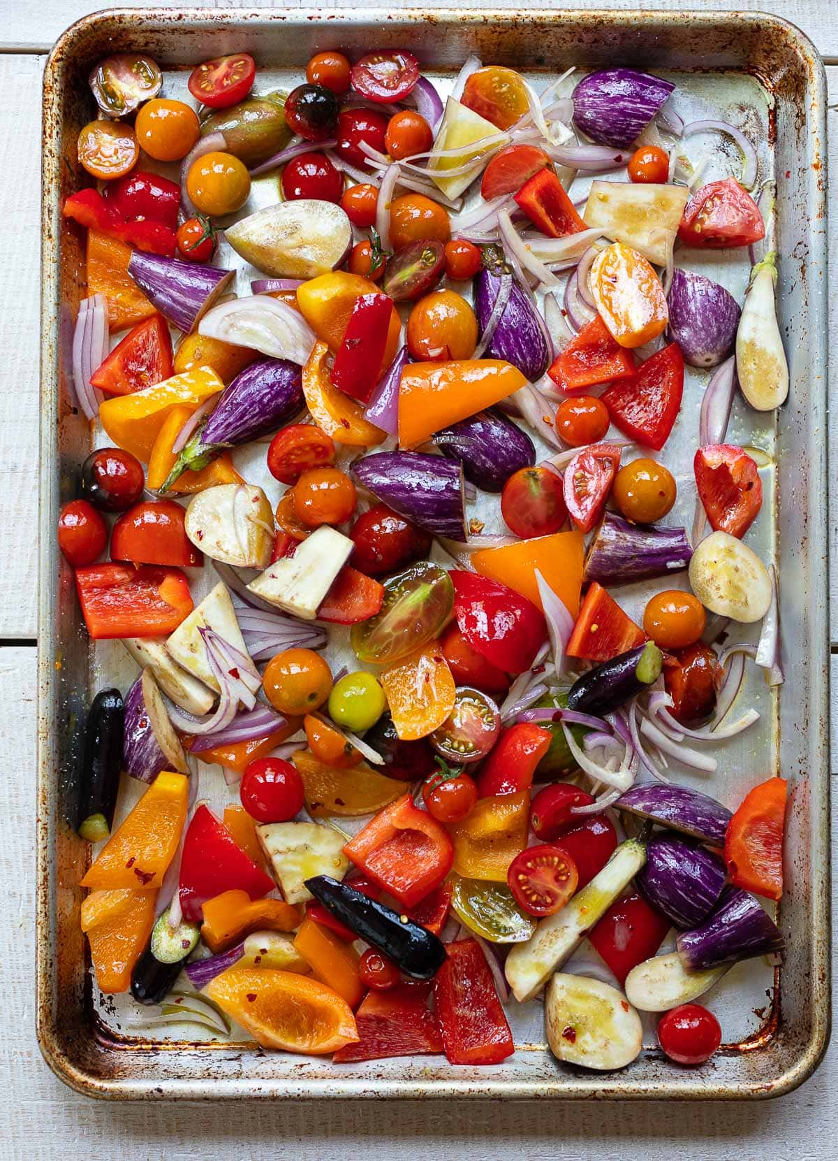 Sheet pan with sliced colorful vegetables prepped for roasting, including purple eggplant, assorted red and orange cherry tomatoes, bell pepper and red onion slices.