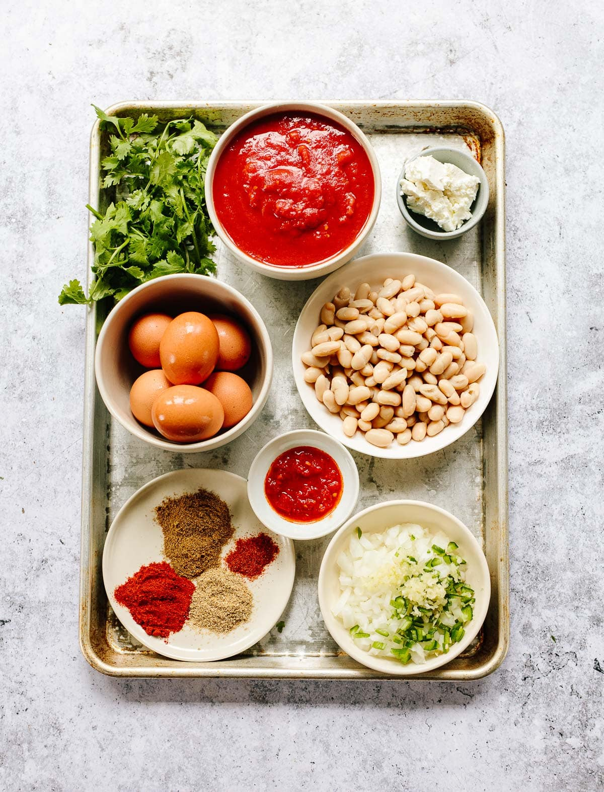 Ingredients on a tray for shakshuka include crushed tomatoes, eggs, cannellini beans, spices, chopped onion, chili, harissa paste and feta cheese.