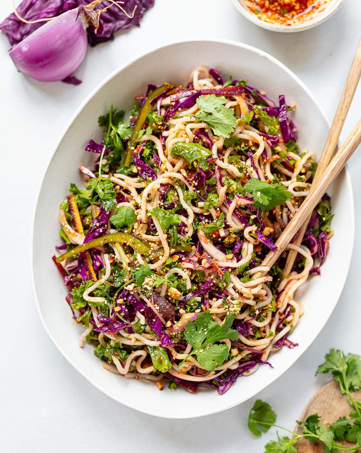 A white oval serving bowl with chopsticks on the side, full of red cabbage and green kale ribbons, bell peppers and Thai noodle slaw with peanuts on top.