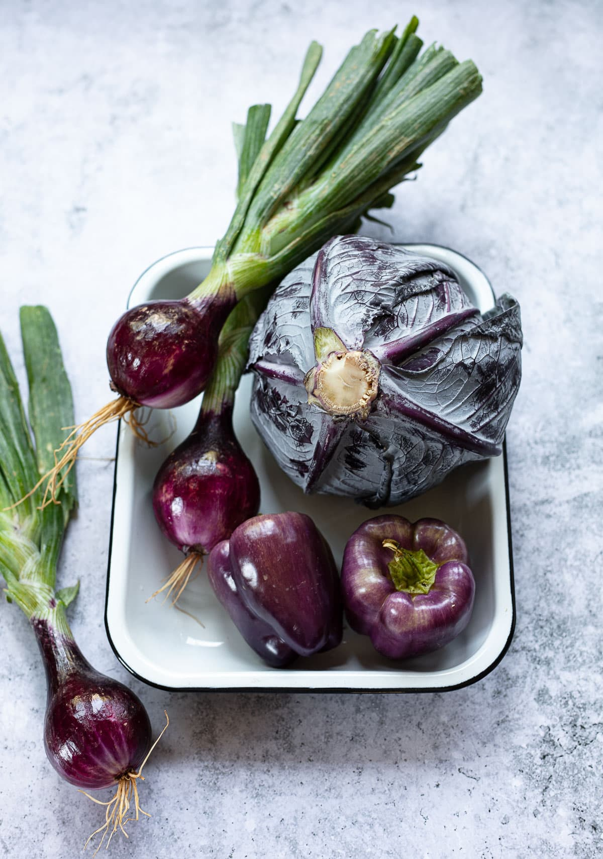 Raw vegetables arranged in a white enamel pan including a whole head of red cabbage, purple bell pepper and red onions.