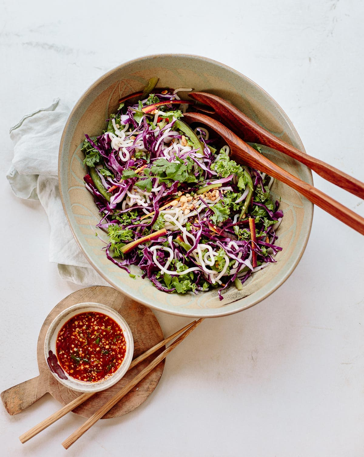 A gray bowl with chopsticks on the side, full of red cabbage and green kale ribbons, bell peppers and Thai noodle slaw with peanuts on top.