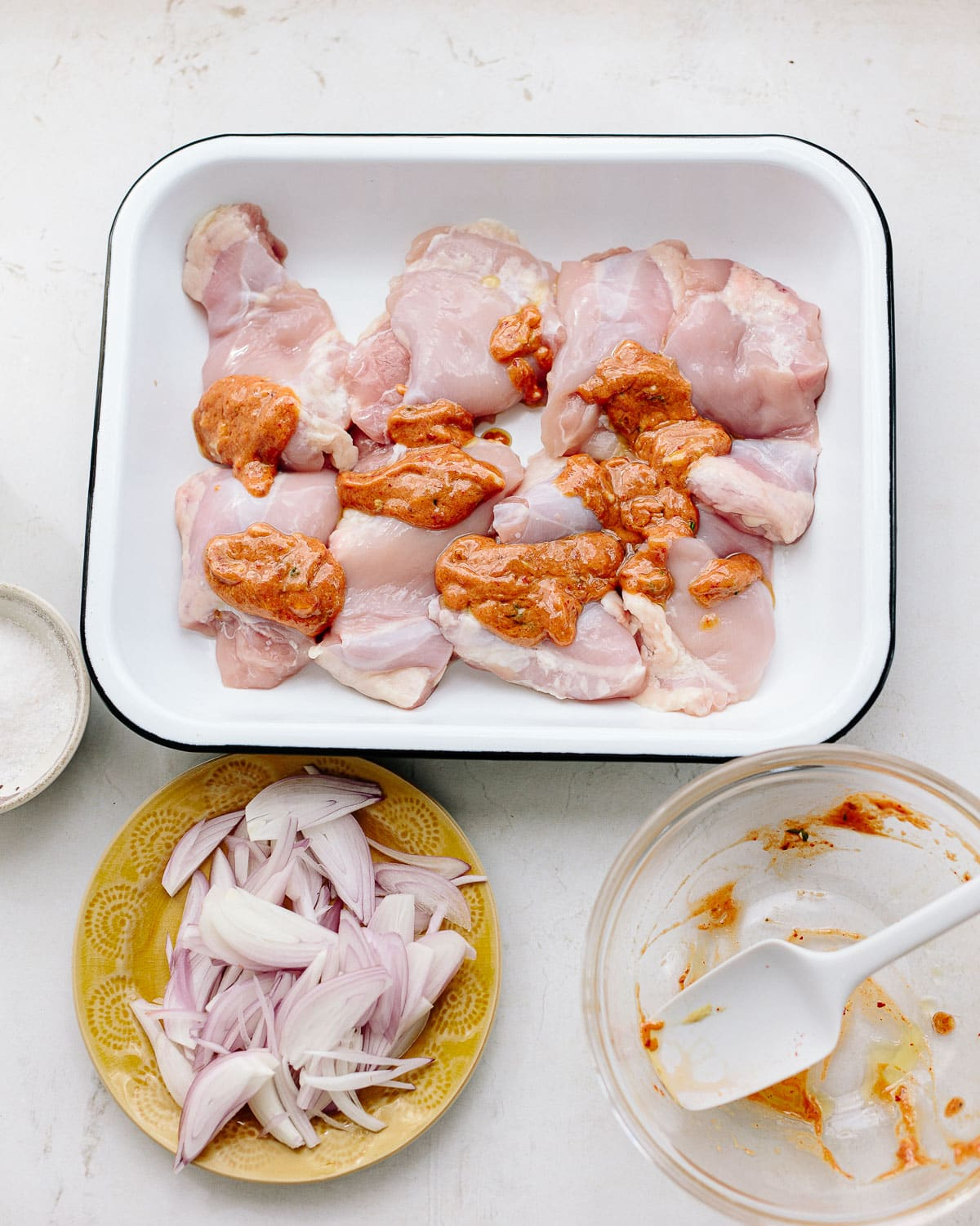 Ingredients to make baked chicken thighs arranged on a tray, with raw boneless skinless chicken pieces, shallots, garlic, mustard, thyme and tomato paste.