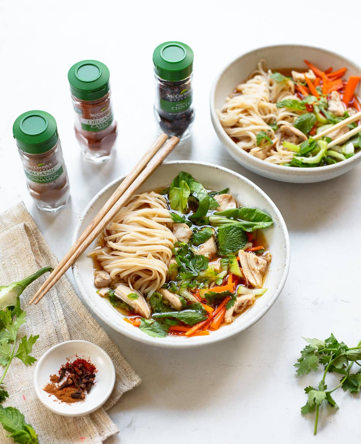 Chicken Pho Noodle Bowl image showing rice noodles, shredded chicken, carrots and herb leaves in spiced chicken broth in a soup bowl, with chopsticks on the side