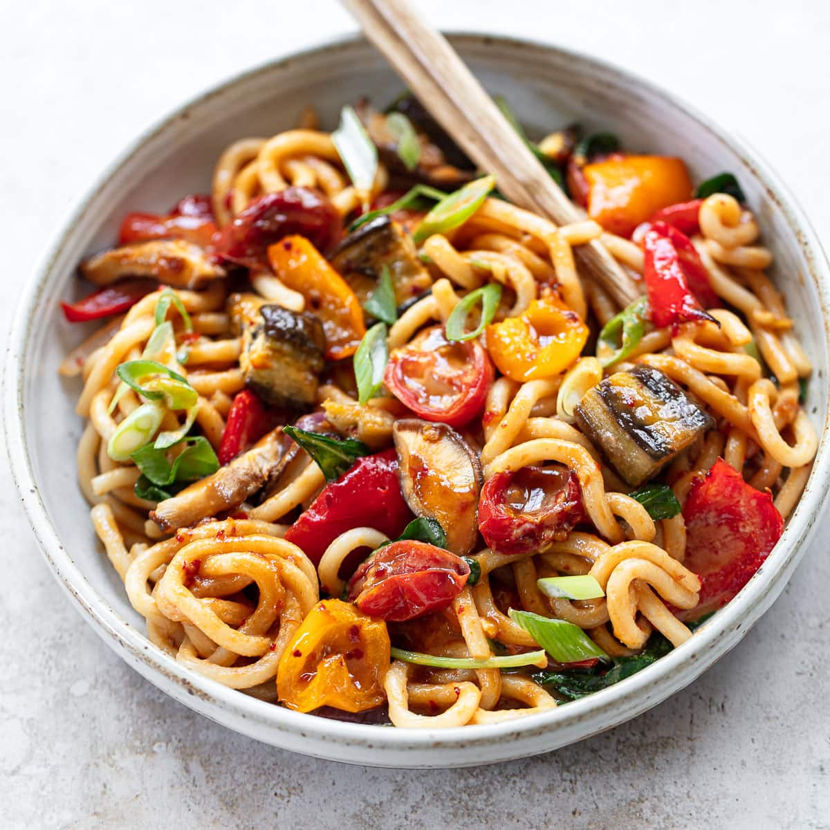 Image of a shallow gray bowl full of udon noodles and roasted vegetables with a pair of chopsticks on the side.