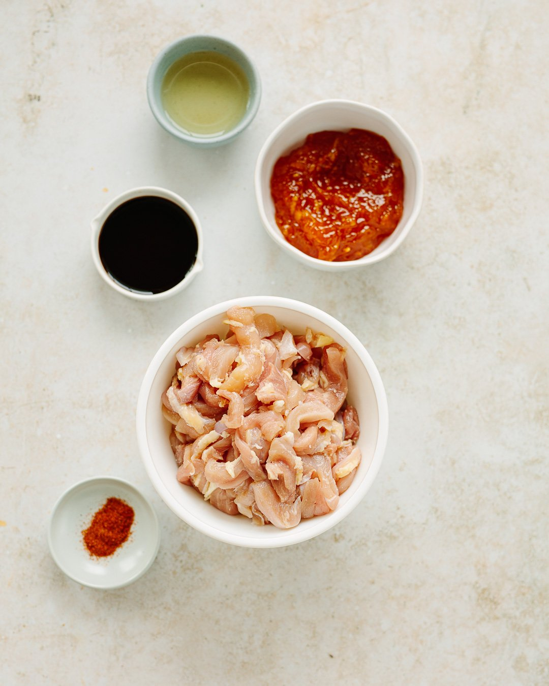 Raw chicken strips with bowls of orange marmalade, rice wine vinegar, soy sauce and cayenne pepper