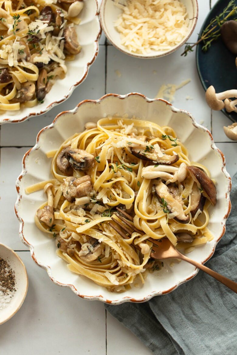 Bowl of fettuccine pasta topped with mushroom sauce, with cheese and forks