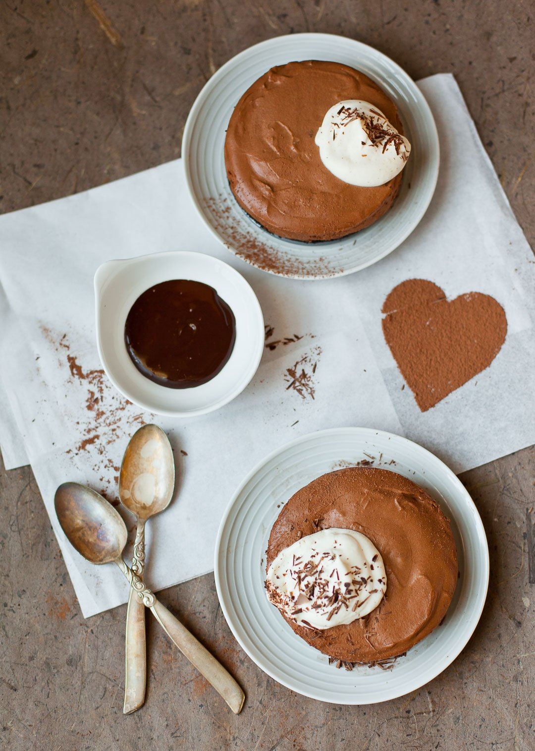 Two plates with spoons holding creamy frozen chocolate semifreddo dessert, topped with soft whipped cream and chocolate shavings.