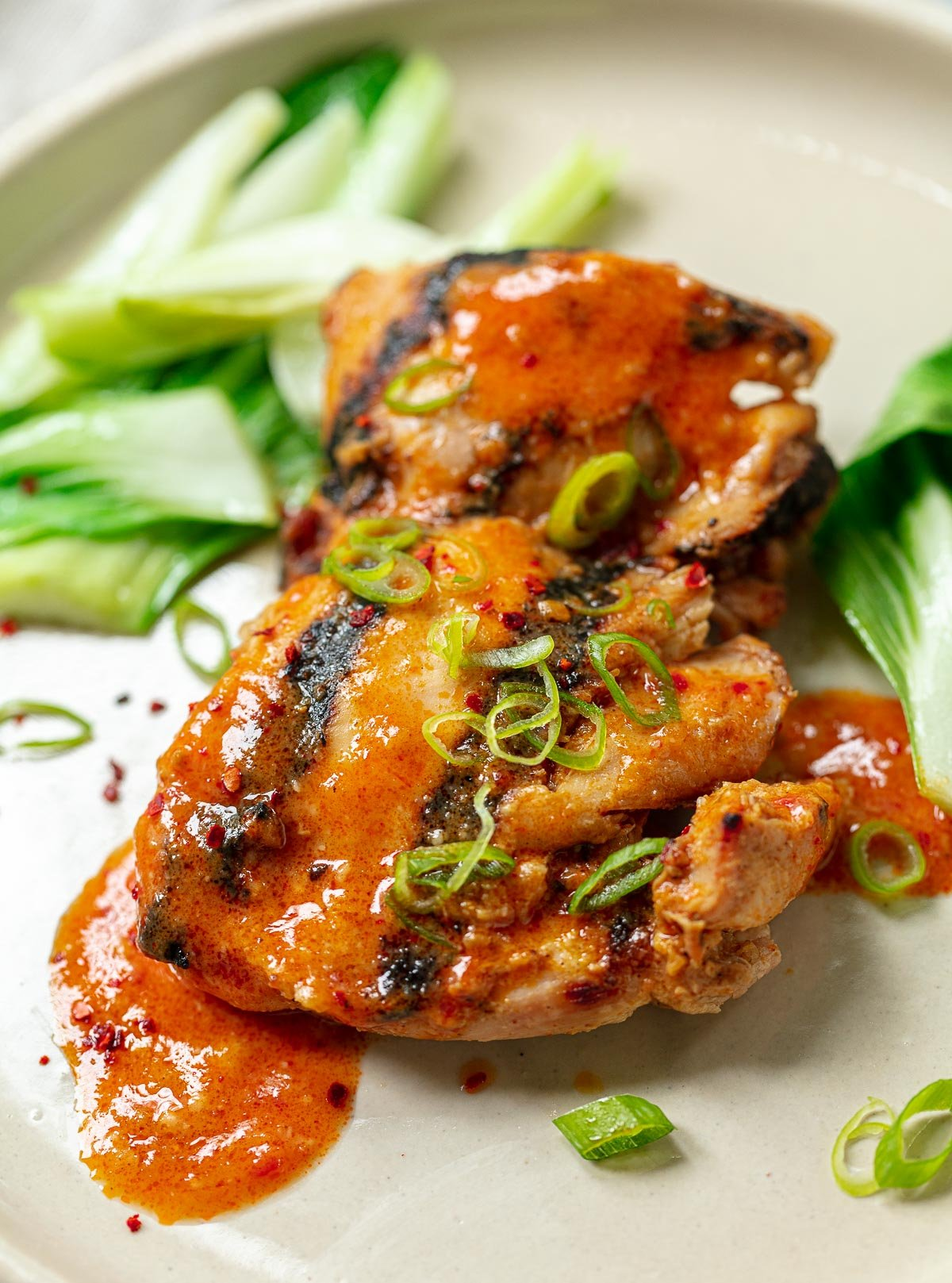 Two glazed chicken thighs on a plate with gochujang sauce and chopped scallion.