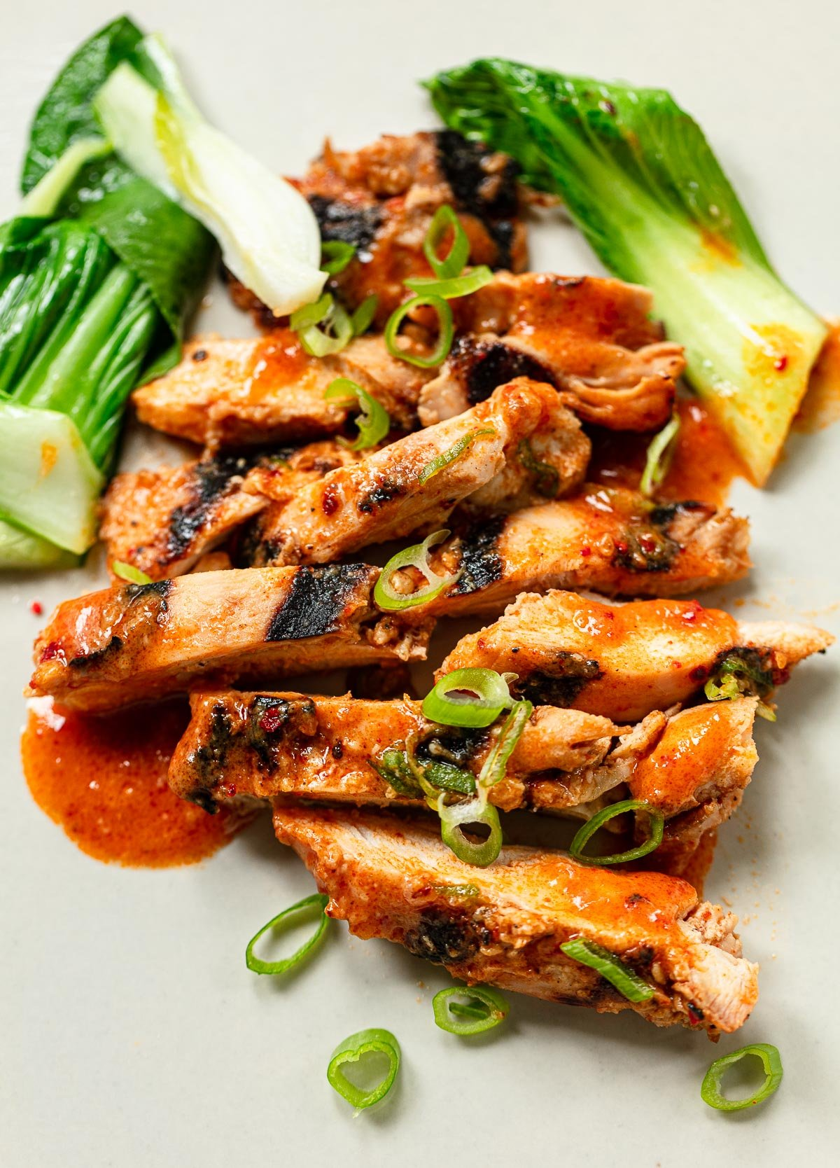 Sliced chicken thighs on a plate with gochujang glaze and chopped scallion.
