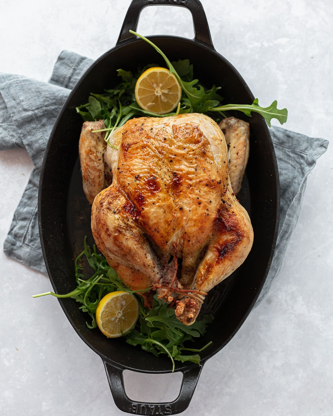 A roasted whole chicken in an oval cast iron baking dish, with lemon and a gray napkin.