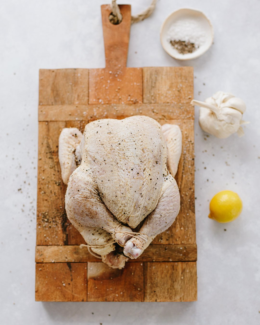 A whole raw chicken prepped on a cutting board with fresh lemons, garlic, thyme and salt and pepper.