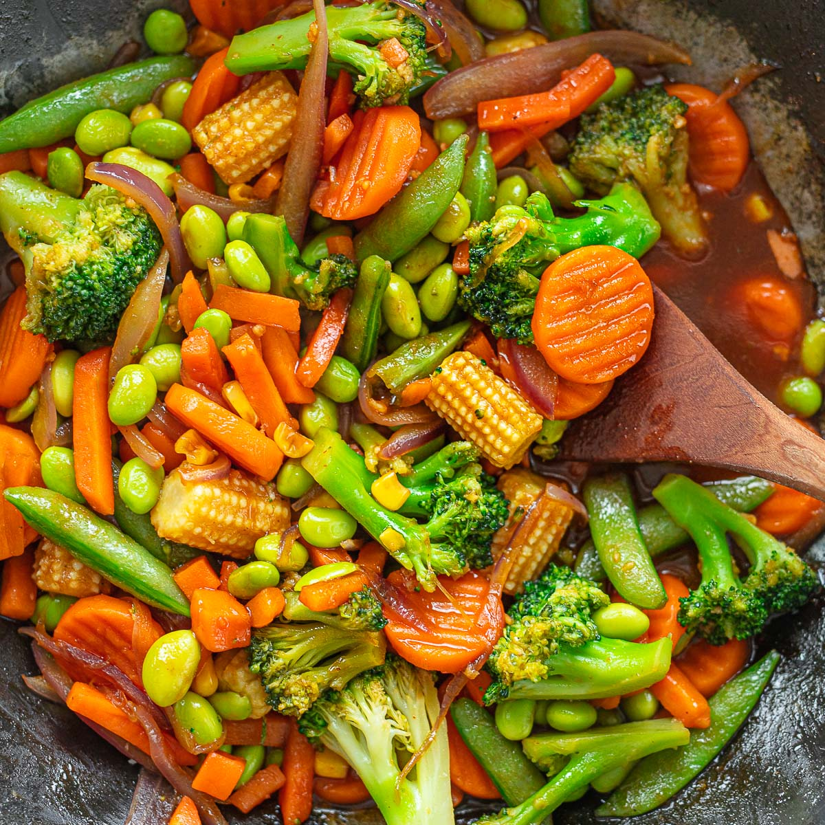 A mixture of stir-fried frozen vegetables in a wok, showing sliced carrots, broccoli florets, baby corn and snap peas.