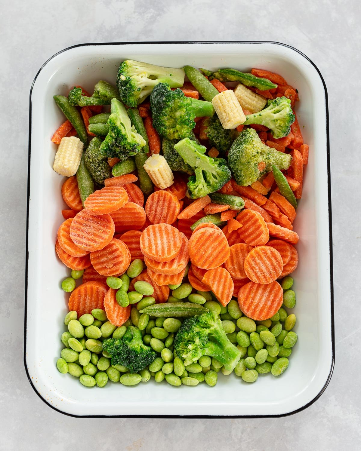A white tray filled with a mixture of frozen broccoli florets, sliced carrots, baby corn, snap peas and edamame.