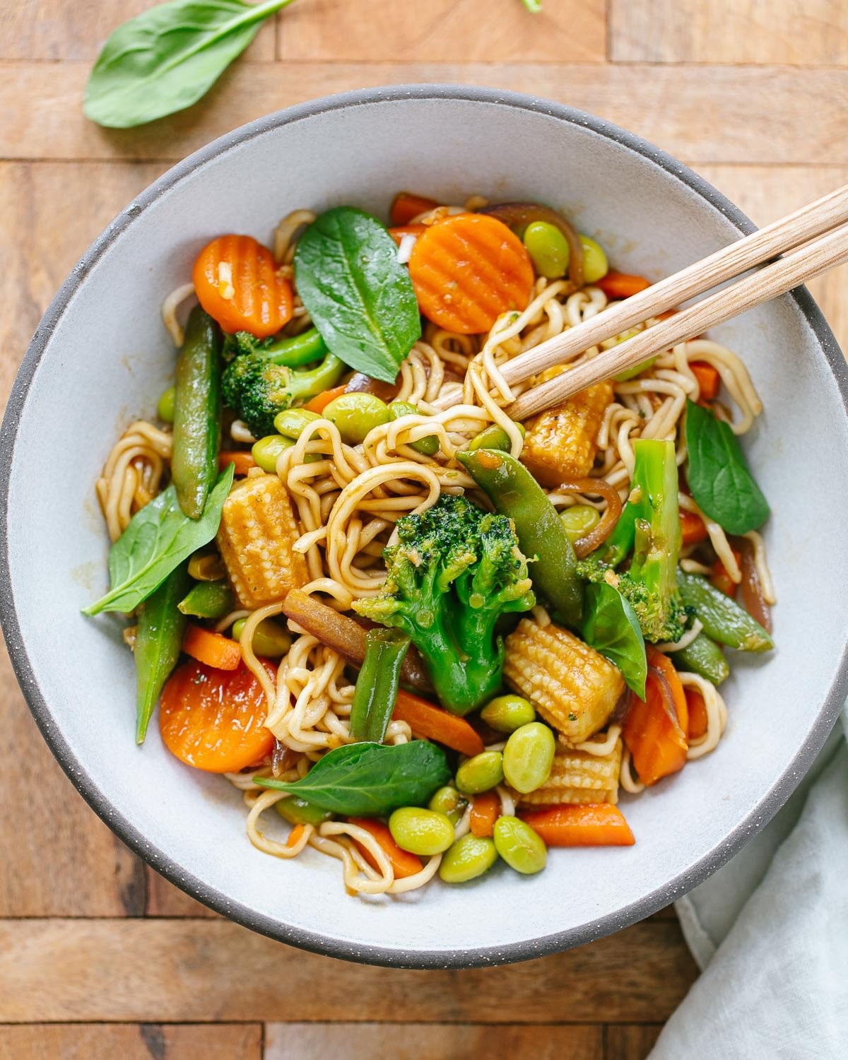A white bowl with chopsticks serving ramen noodles mixed with stir-fried carrots, corn, broccoli, edamame and spinach.