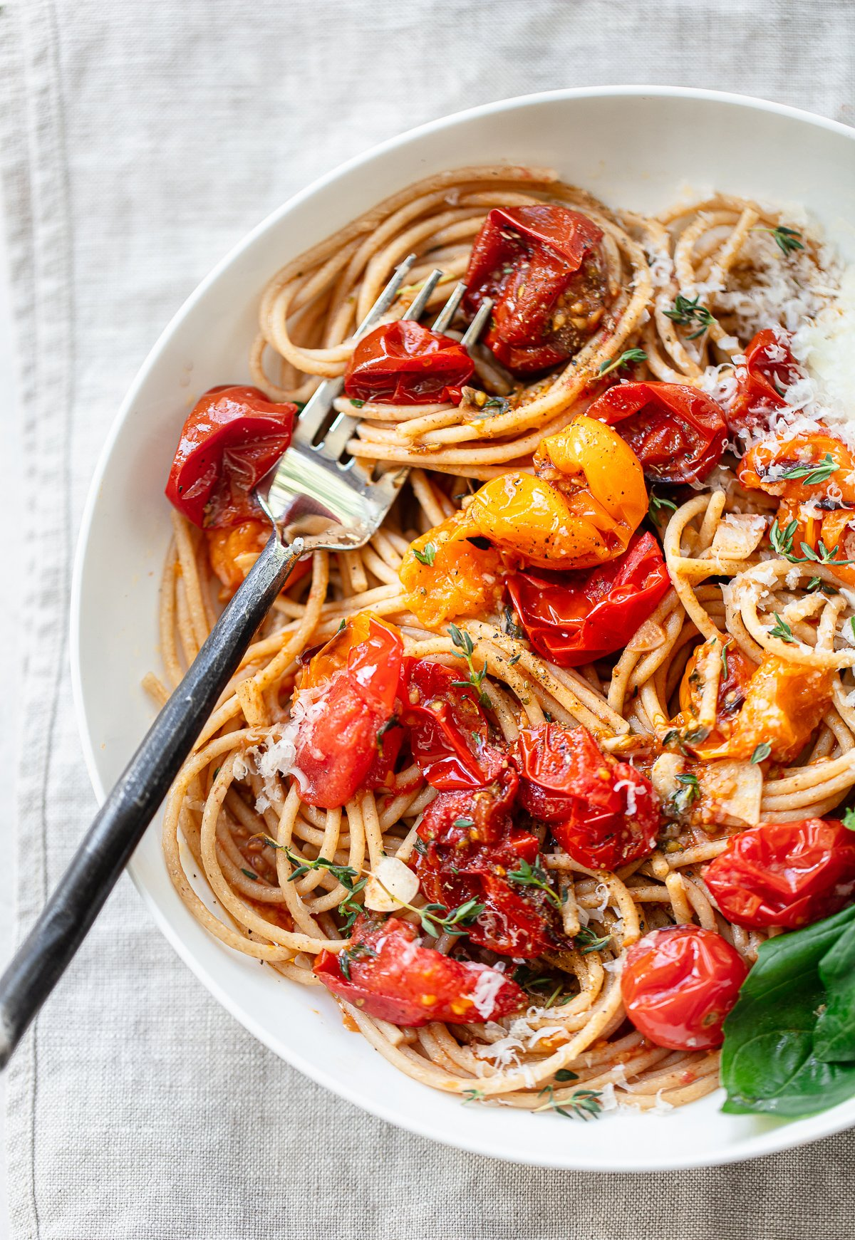 A white bowl filled with spaghetti in a roasted cherry tomato sauce, with fresh basil sprigs and ricotta cheese on the side.